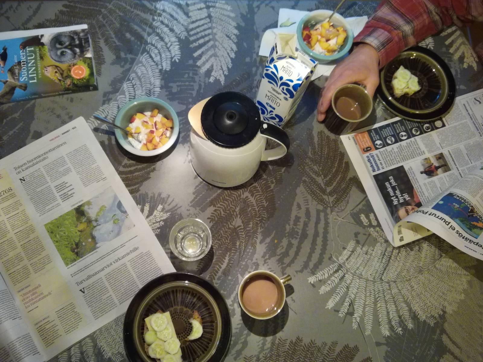 Aamukahvipöydässä avoin sanomalehti, kahvikuppeja ja lintukirja.