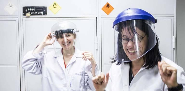Naiset laboratoriotakeissa ja kypärät päässä