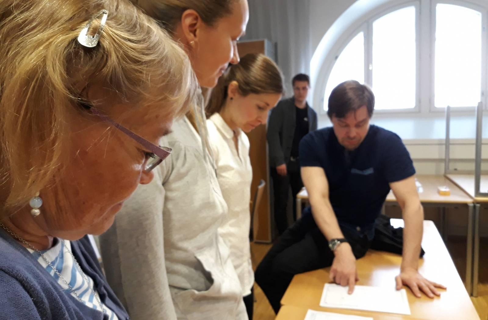 Koordinaatiohankkeen väki tutkii yhdessä papereita.