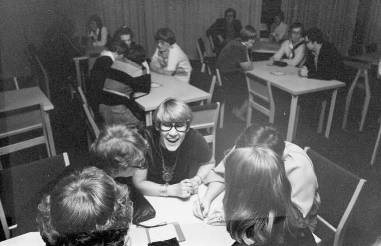 Mustavalkoisessa kuvassa joukko aikuisia ihmisiä istuu pienissä ryhmissä kolmen pöydän ympärillä. Keskellä kuvaa on naurava, vaalea silmälasipäinen ihminen.