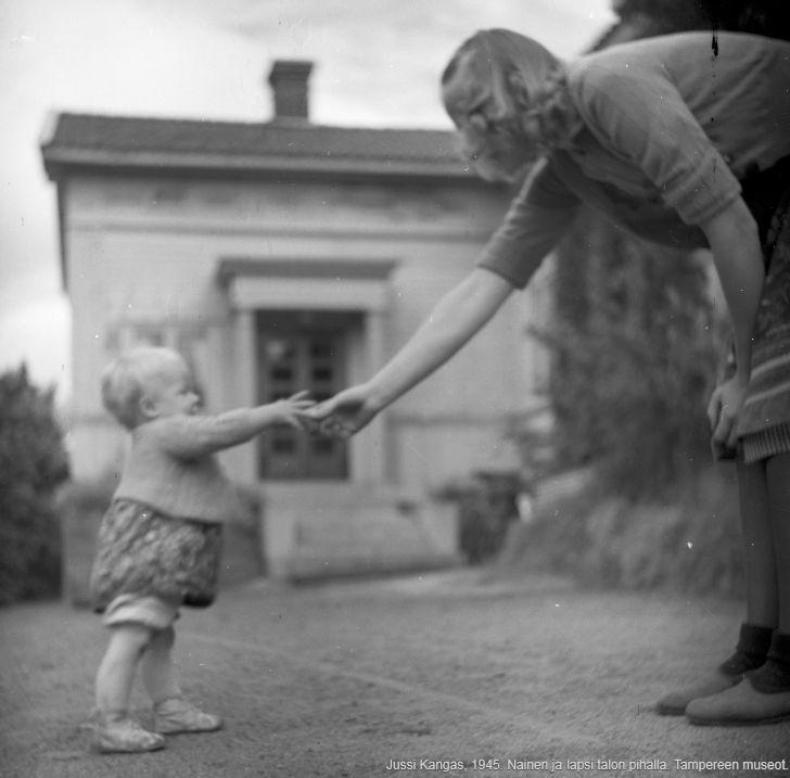 Nainen ja lapsi kurottavat käsiä yhteen talon pihalla. Kuvaaja: Jussi Kangas, 1945. Tampereen museot.