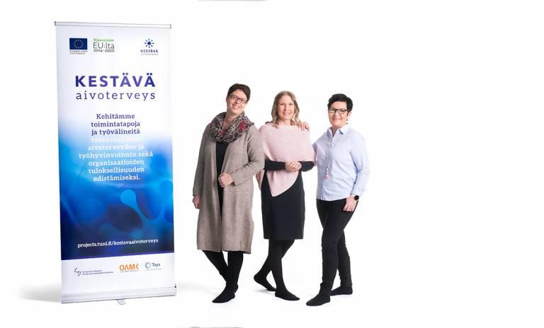Valkoisella taustalla Kestävä aivoterveys -hankkeen rollup ja kolme iloista naista.