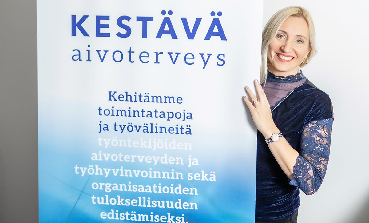 Hymyilevä Kaisa Hartikainen kurkistaa rollupin takaa.