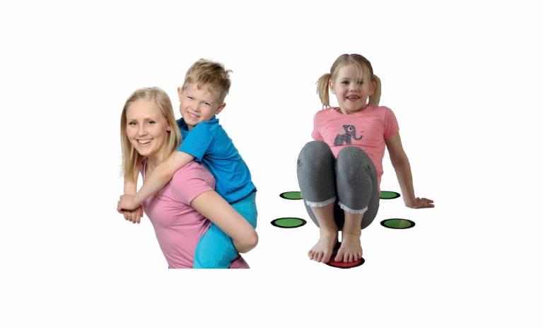 Nainen kantaa reppuselässä poikaa ja pieni tyttö leikkii.