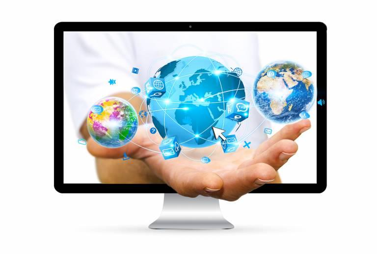 Tietokoneen ruudulta ulos tuleva virtuaalinen käsi, joka kannattelee virtuaalisia maapalloja.