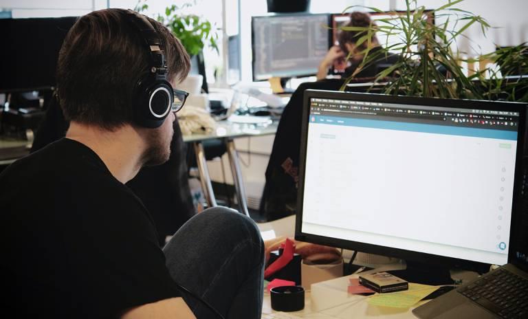 Mustapaitainen henkilö työskentelee tietokoneen näytön äärellä kuulokkeet korvilla.