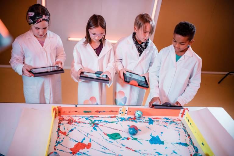 Koululaisia valkoiset laboratoriotakit päällä