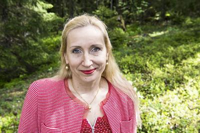Hymyilevä Kaisa Hartikainen punaisessa puserossa ja taustalla vihreää metsää.