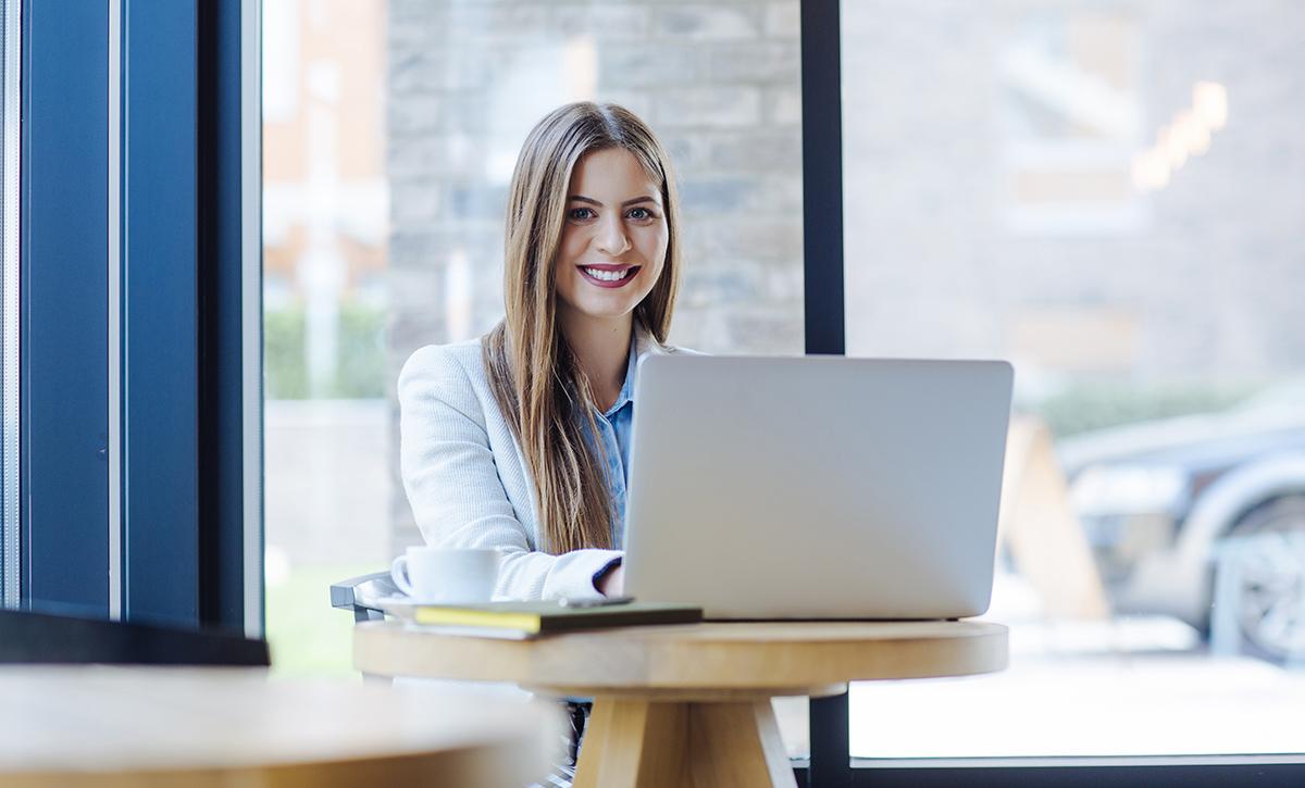 Pitkätukkainen hymyilevä nuori nainen kannettavan tietokoneen ääressä.